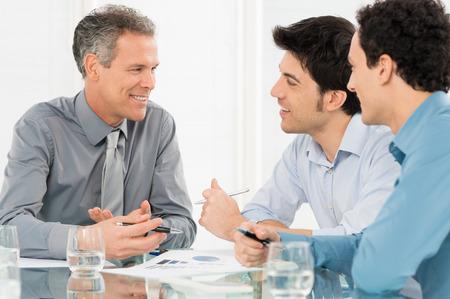 会議の会話をしている幸せなビジネスマンのグループ