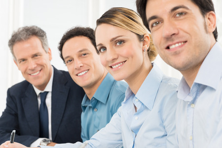 boardroom: Portrait Of Smiling Businesspeople Looking At Camera Sitting In A Row Stock Photo