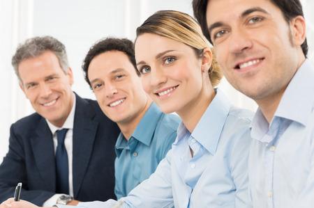 ufficio aziendale: Ritratto Di Sorridente Imprenditori Rivolto verso l'obiettivo seduto in una fila Archivio Fotografico