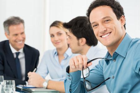 feliz: Retrato de hombre de negocios feliz joven que mira la cámara delante de su colega