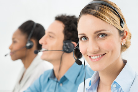 コール センターで他の同僚と作業のヘッドセットを持つ女性の笑みを浮かべてください。 写真素材