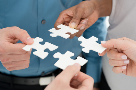 Closeup Businesspeople Hand Holding Jigsaw Puzzle photo