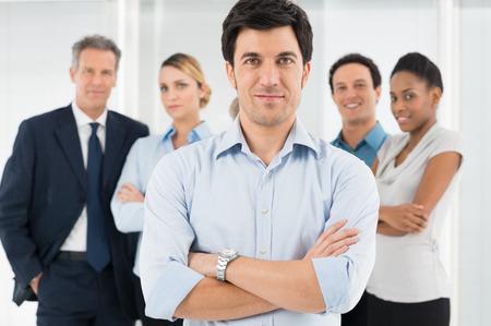 スマートなビジネスマン立っている彼の同僚の前で