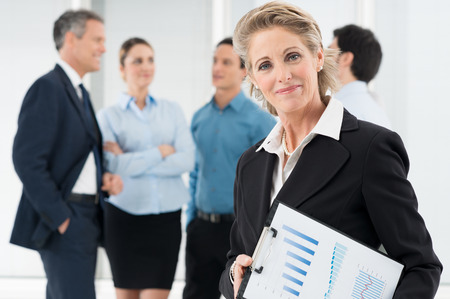 successful leadership: Portrait Of Happy Mature Businesswoman Holding Clipboard