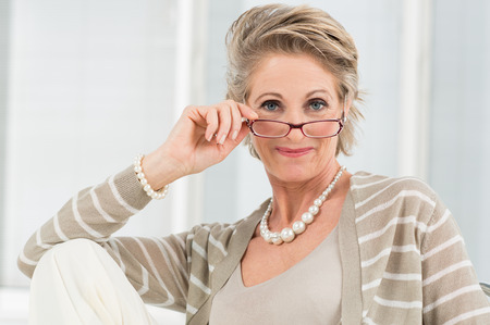 Portrait Of Happy Mature Woman Looking Through Glasses Stok Fotoğraf