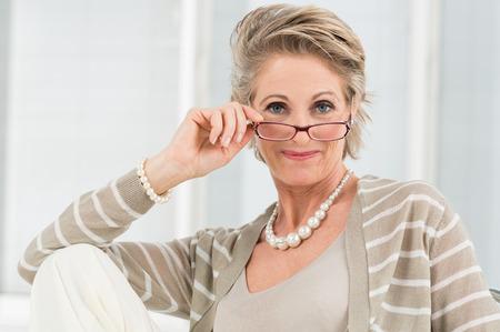 Portret Van Gelukkige Rijpe Vrouw kijkt door een bril