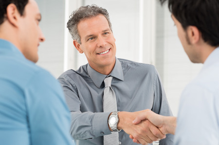 mature people: Portrait Of Mature Man Shaking Hand With Young Businessman Stock Photo