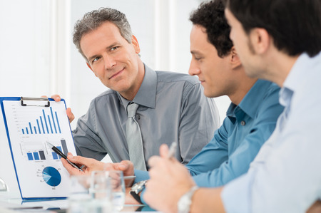 financial planning: Portrait Of Mature Businessman Showing Annual Report Graph To His Colleague