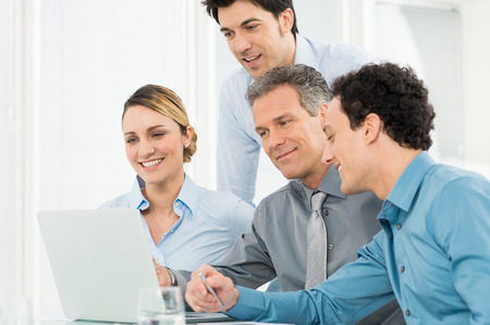 business collaboration: Group Of Happy Businesspeople In Office Looking At Laptop Stock Photo