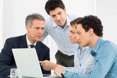 woman serious: Group Of Businesspeople Using Laptop In Meeting Stock Photo