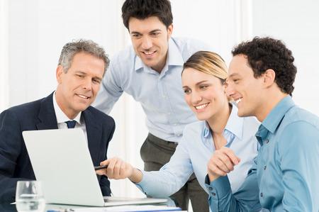Empresaria sonriente joven que muestra Presentación en portátil a su colega Foto de archivo - 27613981