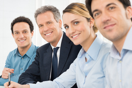 Portrait Of Happy Businesspeople Looking At Camera Sitting In A Row At Office Фото со стока