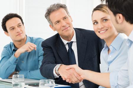 business smile: Dos hombres de negocios acertados que sacuden las manos delante de su colega Foto de archivo