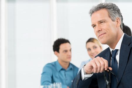 Portrait Of A Thoughtful Mature Businessman Holding Eyeglasses photo