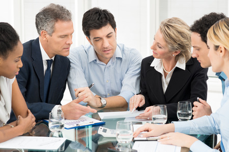 woman serious: Portrait Of Multiracial Businesspeople Brainstorming In Meeting Stock Photo