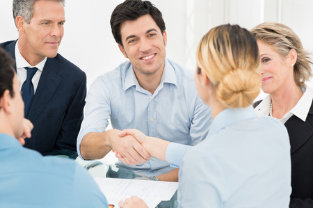 hire: Young Businessman Shaking Hand With Businesswoman In Front Of Colleague Stock Photo