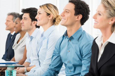 Close Up Of Smiling Multiracial Businesspeople Sitting In A Row photo