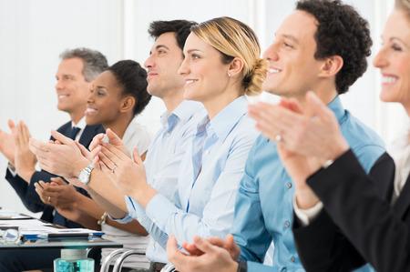 Felice gruppo di imprenditori che applaude in riunione