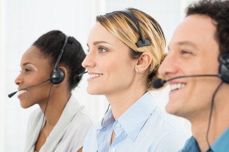 Happy Businesspeople Wearing Headsets Working In Call Center photo