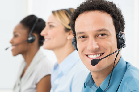 Happy Customer With Headsets Working With Other Colleague In Call Center photo