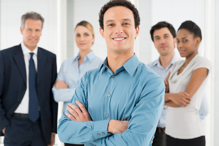 Smiling Businessman With Armcrossed In Front Of Coworker photo
