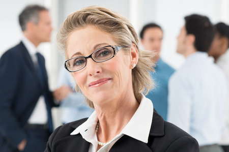 Closeup Of Happy Mature Businesswoman In Front Of Colleague photo