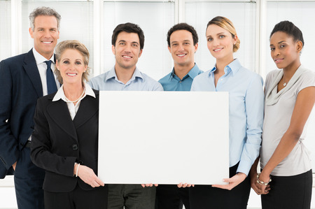 Group Of Happy Multi Ethnic Businesspeople Holding Blank Placard photo