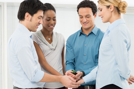 Portrait Of Multi Ethnic Businesspeople Holding Sapling Together photo
