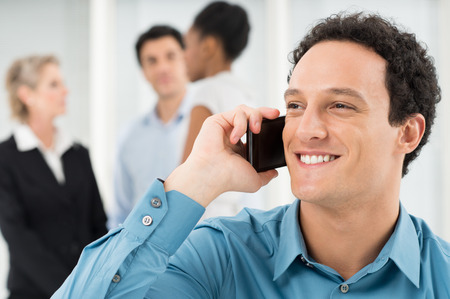 Closeup Of Businessman Talking On Cell Phone In Front Of Colleague photo