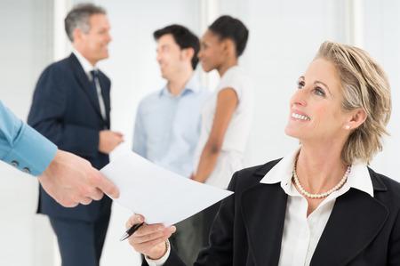 Portrait der lächelnden reifen Geschäftsmann, der Dokument empfehlen