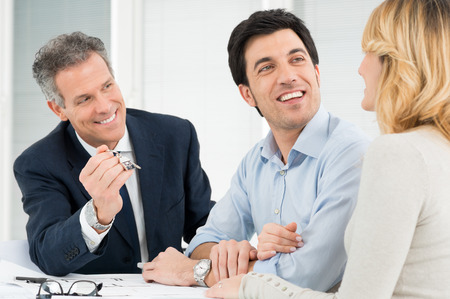 Portrait Of Estate Agent Showing New Home Keys To A Young Couple photo