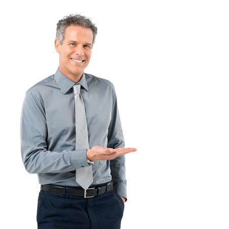 白い背景で隔離の提示する幸せな成熟した実業家の肖像画