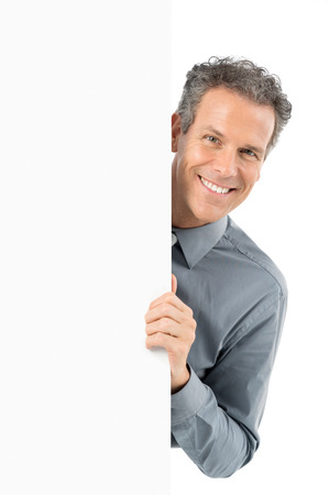 businesspersons: Portrait Of Mature Businessman Holding Blank Billboard Looking At Camera Isolated On White Background