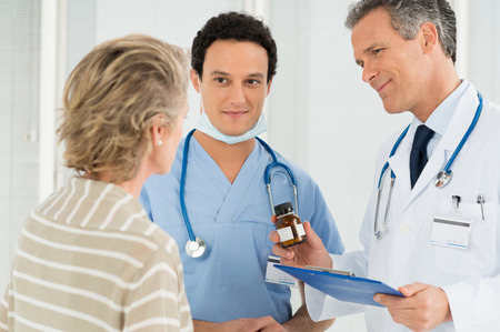 Mature Doctor With Clipboard Prescribing Medication To Mature Woman photo