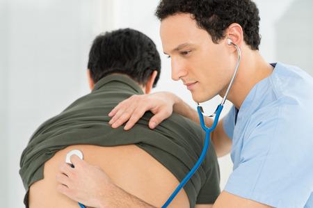 Junge männliche Arzt Überprüfung Patienten mit Stethoskop im Krankenhaus
