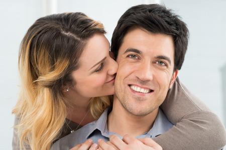 cheek: Portrait Of Young Woman Kissing Man On Cheek