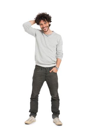 Retrato del hombre joven feliz que se coloca sobre el fondo blanco