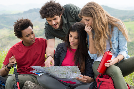 camping equipment: Group Of Multiracial People Worried Looking The Map