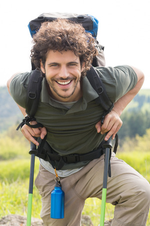 Portrait Of Young Smiling Man Leaning On Hiking Pole Outdoor photo