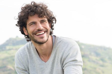 bel homme: Portrait de beau jeune homme souriant en plein air