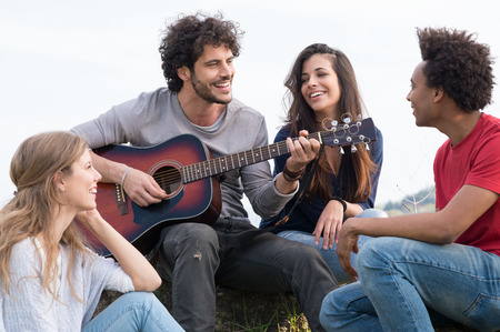 guy playing guitar: Group Of Happy Friends With Guitar Having Fun Outdoor