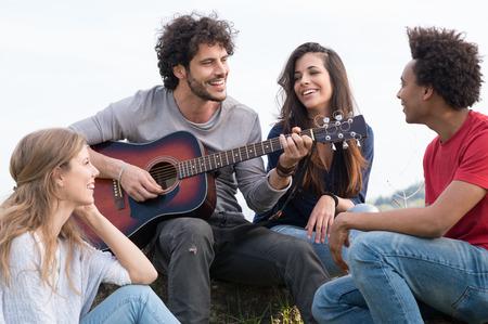 cantando: Grupo de amigos felices con la guitarra que se divierten al aire libre
