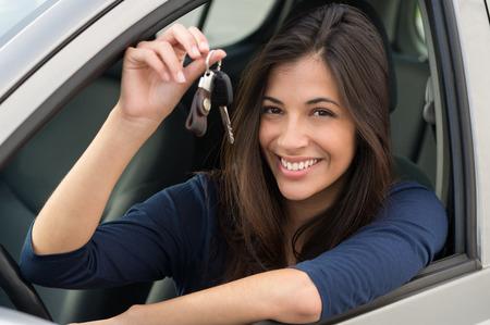 coche: Joven mujer feliz mostrando la clave de nuevos modelos de automóviles