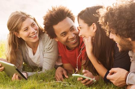 Groupe de jeunes gens multi-tenant tablette numérique et téléphone portable en plein air