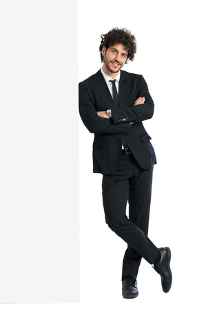 businessman standing: Young Elegant Man Leaning On Billboard Isolated On White Background