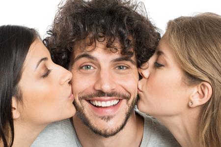 baiser amoureux: Gros plan de deux jeunes femmes Embrasser Handsome Man Banque d'images