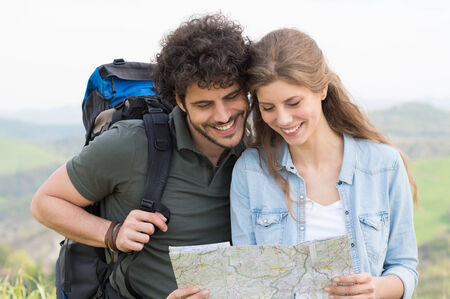 Portrait Of Happy Hikers Analyze The Map In Footpath photo