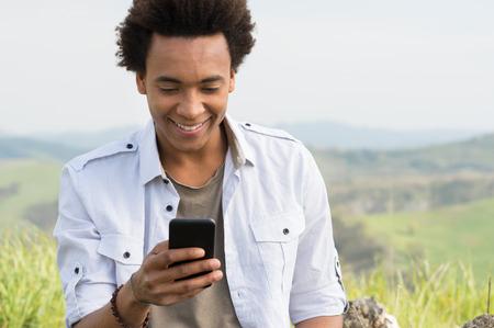 hombre: Hombre africano joven mirando el teléfono móvil Foto de archivo