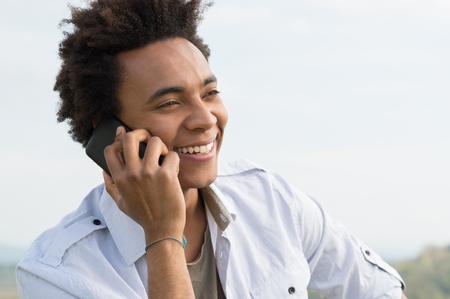 Young Happy African Man Talking On Mobile Phone photo