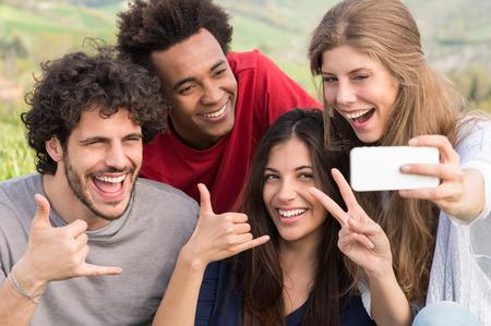 Skupina happy přátel pořízení s mobilním telefonem Outdoor